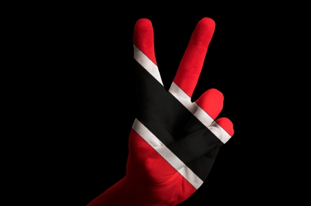 Hand with two finger up gesture in colored trinidad tobago national flag as symbol of winning, victorious, excellent, - for tourism and touristic advertising, positive political, cultural, social management of country photo