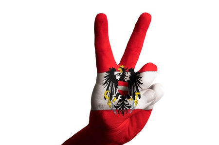 Hand with two finger up gesture in colored austria national flag as symbol of winning, victorious, excellent, - for tourism and touristic advertising, positive political, cultural, social management of country photo