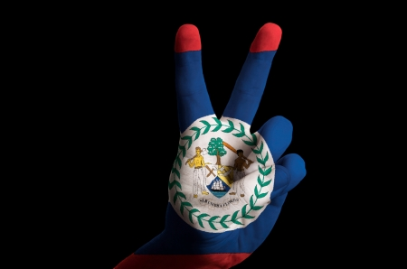 tourism in belize: Hand with two finger up gesture in colored belize national flag as symbol of winning, victorious, excellent, - for tourism and touristic advertising, positive political, cultural, social management of country