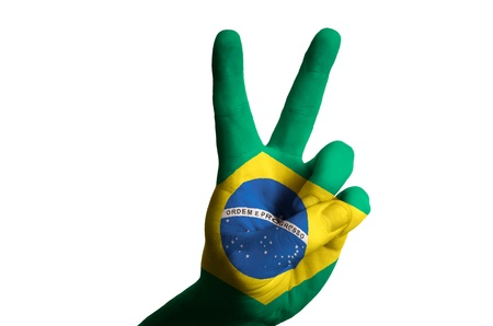 Hand with two finger up gesture in colored brazil national flag as symbol of winning, victorious, excellent, - for tourism and touristic advertising, positive political, cultural, social management of country
