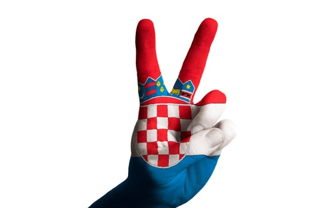 Hand with two finger up gesture in colored croatia national flag as symbol of winning, victorious, excellent, - for tourism and touristic advertising, positive political, cultural, social management of country photo