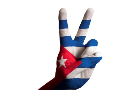 Hand with two finger up gesture in colored cuba national flag as symbol of winning, victorious, excellent, - for tourism and touristic advertising, positive political, cultural, social management of country photo