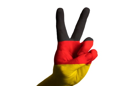 Hand with two finger up gesture in colored germany national flag as symbol of winning, victorious, excellent, - for tourism and touristic advertising, positive political, cultural, social management of country photo