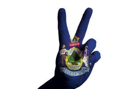 Hand with two finger up gesture in colored maine state flag as symbol of winning, victorious, excellent, - for tourism and touristic advertising, positive political, cultural, social management of country photo