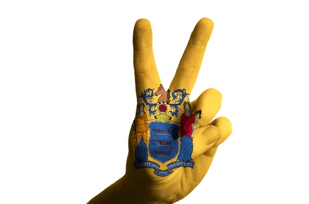 Hand with two finger up gesture in colored new jersey state flag as symbol of winning, victorious, excellent, - for tourism and touristic advertising, positive political, cultural, social management of country photo