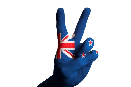 Hand with two finger up gesture in colored new zealand national flag as symbol of winning, victous, excellent, - for tourism and touristic advertising, positive political, cultural, social management of country Stock Photo - 15001516