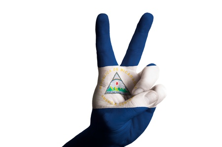 Hand with two finger up gesture in colored nicaragua national flag as symbol of winning, victorious, excellent, - for tourism and touristic advertising, positive political, cultural, social management of country photo
