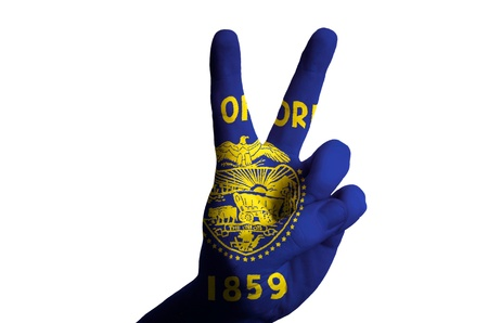 Hand with two finger up gesture in colored oregon american state flag as symbol of winning, victorious, excellent, - for tourism and touristic advertising, positive political, cultural, social management of country photo