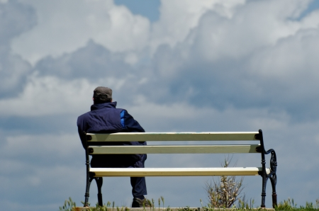 Working man during break sitting on bench and watching into sky