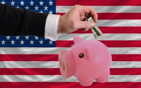 foreign national: Man putting dollar into piggy rich bank national flag of us in foreign currency because of inflation Stock Photo