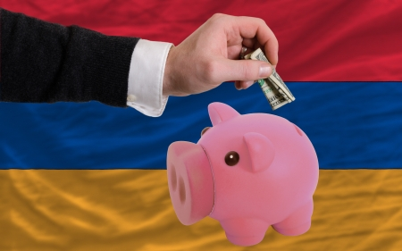 foreign national: Man putting dollar into piggy rich bank national flag of armenia in foreign currency because of inflation Stock Photo
