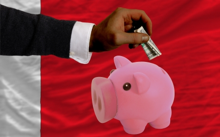 foreign national: Man putting dollar into piggy rich bank national flag of bahrain in foreign currency because of inflation Stock Photo