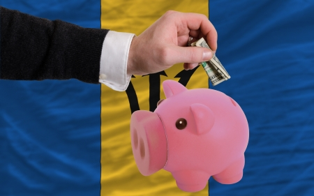foreign national: Man putting dollar into piggy rich bank national flag of barbados in foreign currency because of inflation Stock Photo