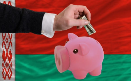 foreign national: Man putting dollar into piggy rich bank national flag of belarus in foreign currency because of inflation Stock Photo