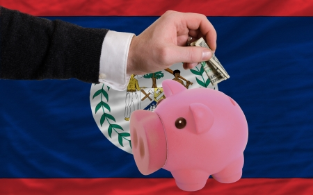 foreign national: Man putting dollar into piggy rich bank national flag of belize in foreign currency because of inflation