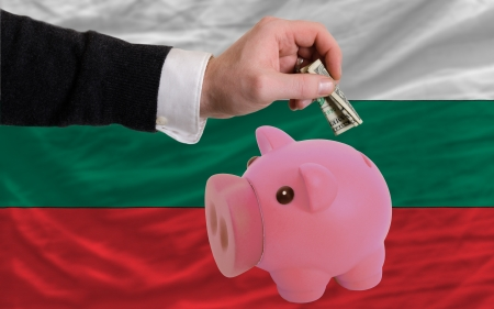 foreign national: Man putting dollar into piggy rich bank national flag of bulgaria in foreign currency because of inflation Stock Photo