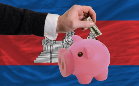 foreign national: Man putting dollar into piggy rich bank national flag of cambodia in foreign currency because of inflation