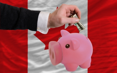 foreign national: Man putting dollar into piggy rich bank national flag of canada in foreign currency because of inflation