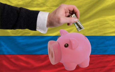 foreign national: Man putting dollar into piggy rich bank national flag of columbia in foreign currency because of inflation