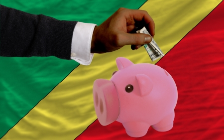 foreign national: Man putting dollar into piggy rich bank national flag of  congo in foreign currency because of inflation Stock Photo
