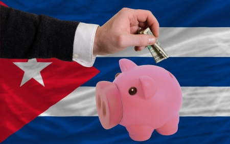 foreign national: Man putting dollar into piggy rich bank national flag of cuba in foreign currency because of inflation