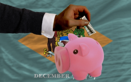 Man putting dollar into piggy rich bank flag of us state of delaware in foreign currency because of inflation photo