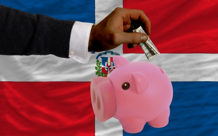 foreign national: Man putting dollar into piggy rich bank national flag of dominican in foreign currency because of inflation
