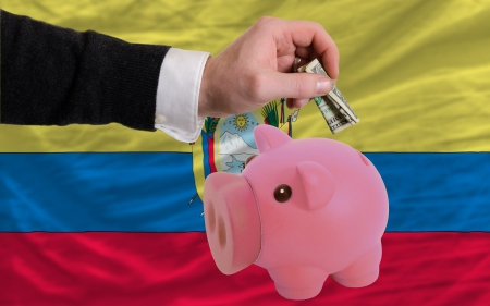 foreign national: Man putting dollar into piggy rich bank national flag of ecuador in foreign currency because of inflation Stock Photo