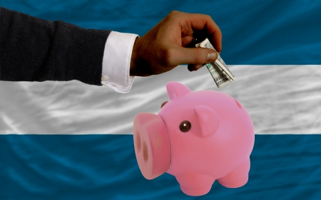 foreign national: Man putting dollar into piggy rich bank national flag of el salvador in foreign currency because of inflation