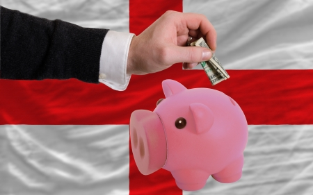 foreign national: Man putting dollar into piggy rich bank national flag of england in foreign currency because of inflation