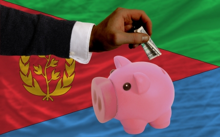 foreign national: Man putting dollar into piggy rich bank national flag of  eritrea in foreign currency because of inflation