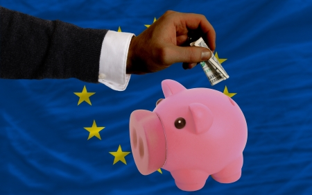 foreign national: Man putting dollar into piggy rich bank national flag of europe in foreign currency because of inflation