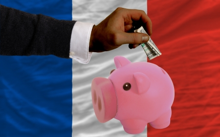Man putting dollar into piggy rich bank national flag of france in foreign currency because of inflation photo