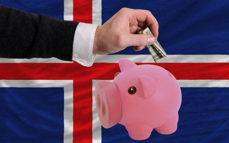 foreign national: Man putting dollar into piggy rich bank national flag of iceland in foreign currency because of inflation Stock Photo