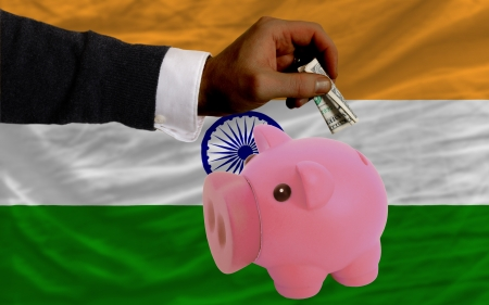 foreign national: Man putting dollar into piggy rich bank national flag of  india in foreign currency because of inflation Stock Photo