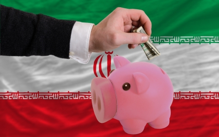 foreign national: Man putting dollar into piggy rich bank national flag of iran in foreign currency because of inflation