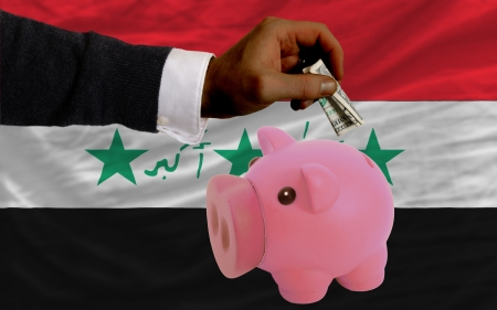iraq money: Man putting dollar into piggy rich bank national flag of iraq in foreign currency because of inflation