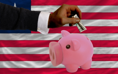 foreign national: Man putting dollar into piggy rich bank national flag of liberia in foreign currency because of inflation