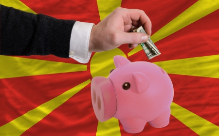 foreign national: Man putting dollar into piggy rich bank national flag of macedonia in foreign currency because of inflation Stock Photo