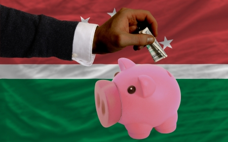 foreign national: Man putting dollar into piggy rich bank national flag of  maghreb in foreign currency because of inflation