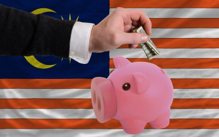 foreign national: Man putting dollar into piggy rich bank national flag of malaysia in foreign currency because of inflation Stock Photo