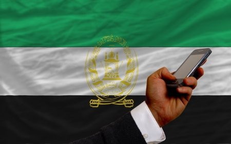 man holding cell phone in front national flag of afghanistan symbolizing mobile communication and telecommunication Stock Photo - 17921507