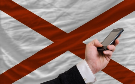 telecommuniation: man holding cell phone in front flag of us state of alabama symbolizing mobile communication and telecommunication