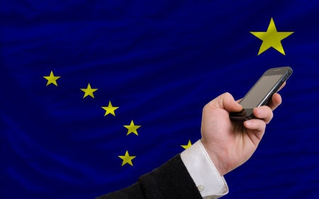 man holding cell phone in front flag of us state of alaska symbolizing mobile communication and telecommunication Stock Photo