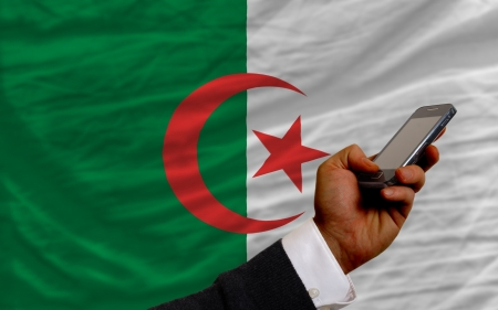 man holding cell phone in front national flag of algeria symbolizing mobile communication and telecommunication Stock Photo