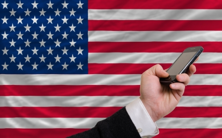 man holding cell phone in front national flag of us symbolizing mobile communication and telecommunication Stock Photo