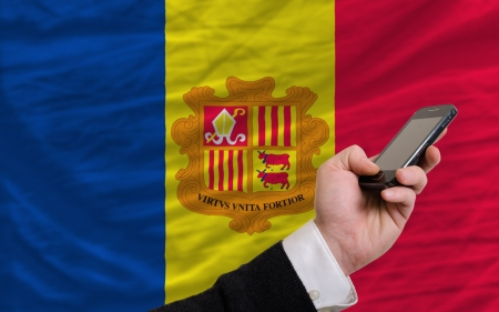 man holding cell phone in front national flag of andorra symbolizing mobile communication and telecommunication