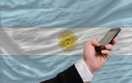 man holding cell phone in front national flag of argentina symbolizing mobile communication and telecommunication