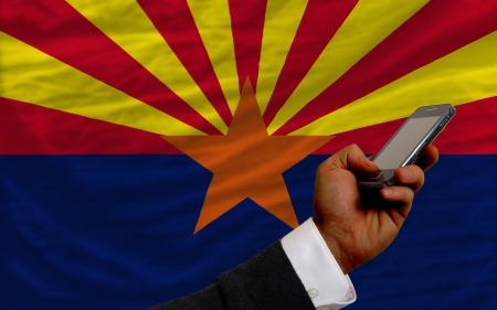telecommuniation: man holding cell phone in front flag of us state of arizona symbolizing mobile communication and telecommunication Stock Photo