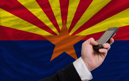 man holding cell phone in front flag of us state of arizona symbolizing mobile communication and telecommunication Stock Photo